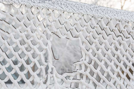 A large hole in the metal mesh of the snow-covered fence.