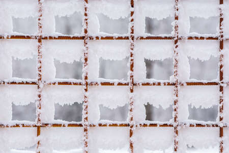 Snow-covered large cells of the rusty metal mesh of the fence. Standard-Bild