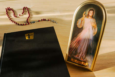 Catholic attributes. Icon of the Merciful Jesus, the Bible and the Holy Rosary.