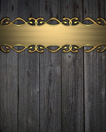 Gold plaque with gold patterns on a wooden background  nameplate for the label  photo