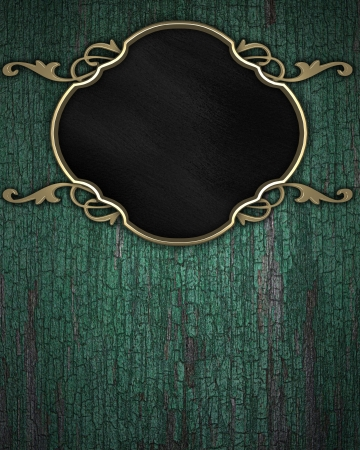 Gold Pattern on a black plate on a wood background photo