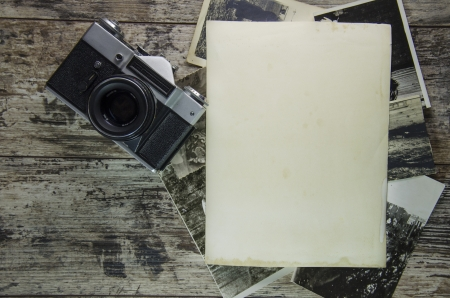 retro still camera and some old photos on wooden table background. Stock Photo