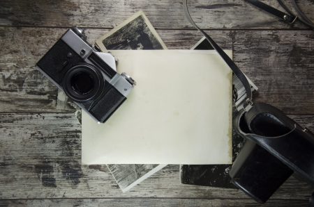 retro still camera and some old photos on wooden table background. Stock Photo - 17346247