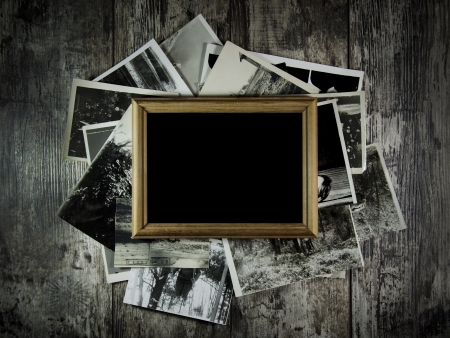 Photo frame with lots of photos lying on an old table. photo