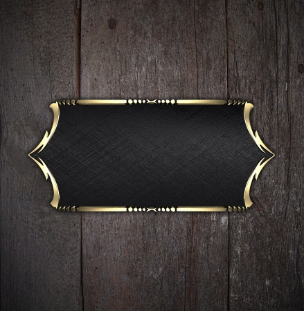 Template for writing. Black nameplate with gold ornate edges, on wooden background photo