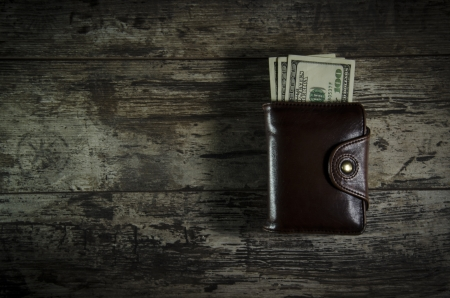 Wallet with hundred dollar banknotes, on wooden background photo