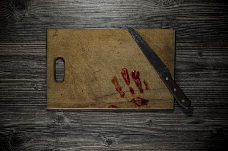 bloody hand print: Grunge fondo de madera con una impresi�n de la mano sangrienta en la tabla de cortar