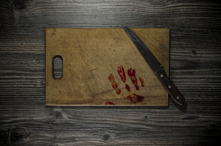 Grunge wooden background with a bloody hand print on the cutting board photo
