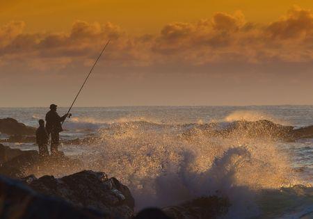 hombre pescando: Una escena de la pesca de la roca en la salida del sol.