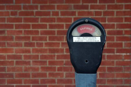 An expired parking meter with brick wall background.