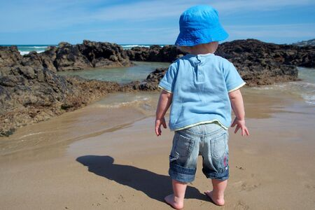 A young child on the beach, shot from behind. photo