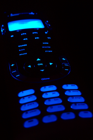 vcr: A glowing remote control on black background.