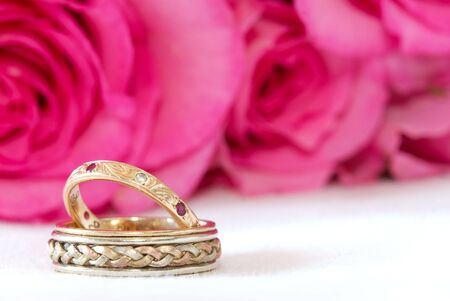 green gemstone: A pair of wedding rings with a pink rose background.