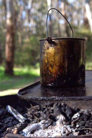 billy: A bush campfire, with a billy boiling on the hot plate.