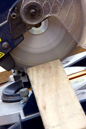 miter: A powered drop saw cutting timber on a construction site.