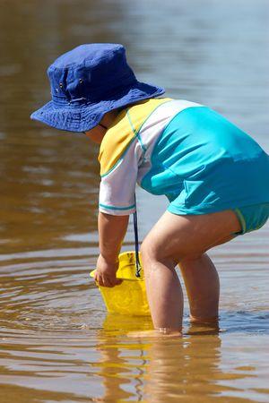 niño abrigado: Un niño jugando en la playa para protegerse del sol usando ropa.