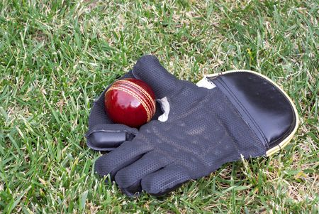 Wicket keeping glove with a new red cricket ball before play. Stock Photo