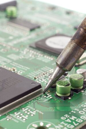 Eectronic circuit board repair with soldering iron. Stock Photo