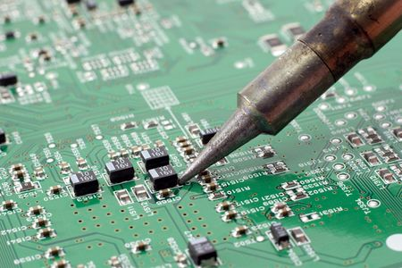 Technician repairing electronic circuit board with soldering iron. Stock Photo
