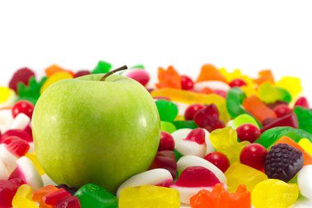 obesidad infantil: Una nueva manzana verde sobre un fondo de una variedad de dulces.