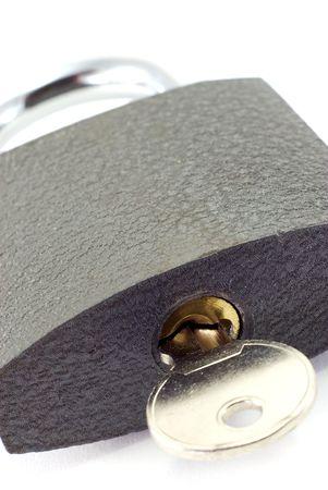 A close-up of key inside a padlock.