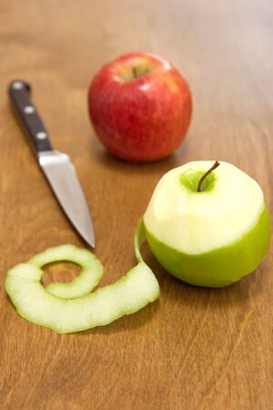 paring knife: Green and red apples on a wooden chopping board.