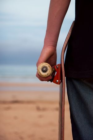 A skateboarder holding his board. Beach background with plenty of copy-space. Stock Photo