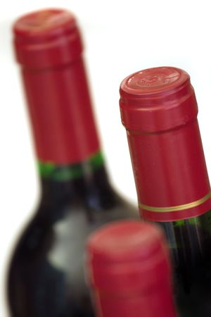 Three unopened wine bottles, isolated on white. Focus on middle bottlecap.