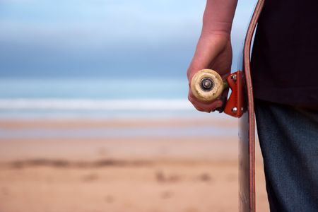 A skater holding his board. beach background with plenty of copy-space. Focus on wheel and board.