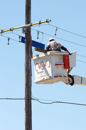 utility pole: A linesman performing maintenance on power lines. Stock Photo