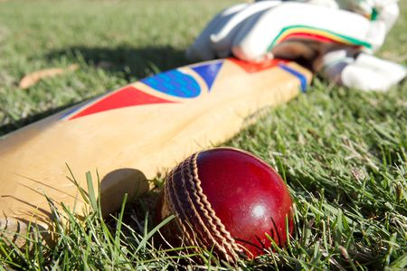 Cricket ball, bat and gloves on the field. Reklamní fotografie
