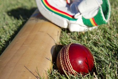 cricket field: Cricket ball, bat and gloves on the field. Stock Photo