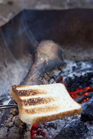 Toasting bread over hot coals in a campfire. Stock Photo - 2860901