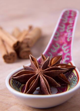 asian flavors: Star anise on an asian spoon with cinnamon sticks in the background. Stock Photo