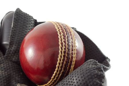 keeping: Wicket keeping glove with a new red cricket ball, isolated on white.