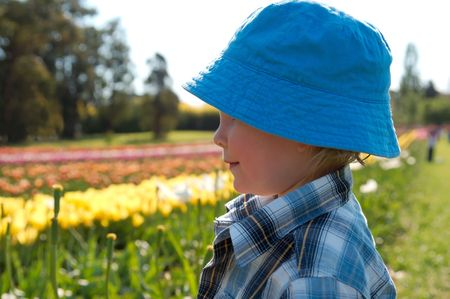 A young boy standing in a field of tulips, wearing sun protection. photo
