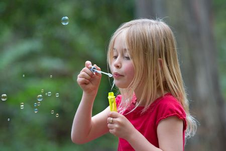 girl blowing: A gorgeous young girl blowing bubbles outdoors. Stock Photo