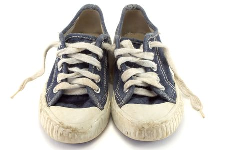 An old worn pair of childrens jogging shoes.