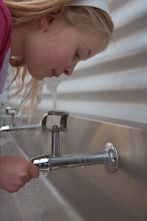 A young school girl drinking from bubble taps. photo