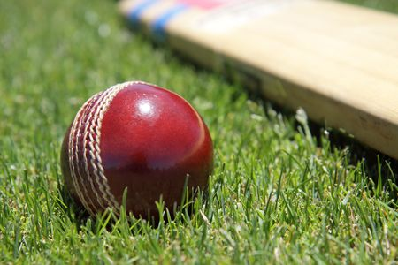 cricket game: New cricket ball and bat on green grass.