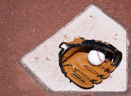 A baseball glove and ball resting on the plate. photo