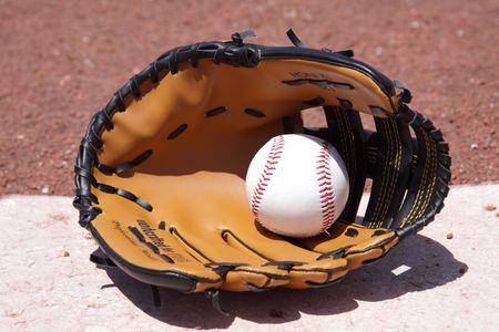 A baseball glove and ball on the plate. photo