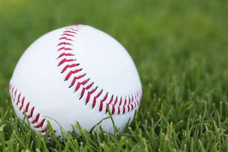 A close-up of a new baseball on green grass.