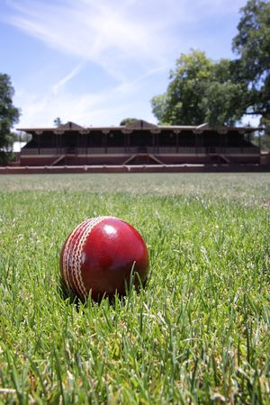grand hard: Shiny new cricket ball on grass in front of grand stand.