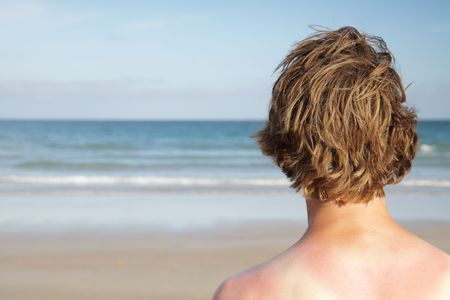 sunburnt: A sunburnt surfer looks out to the ocean. Stock Photo