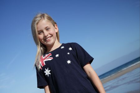 australian: A young girl wearing an Australian flag t-shirt at the beach.