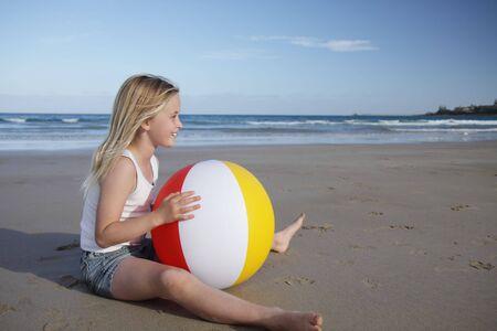 beachball: A young girl plays with a beach ball on the sand.