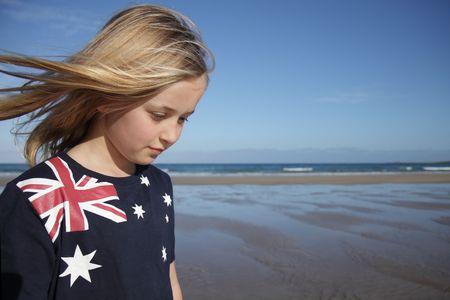 A young girl wearing an Australian flag t-shirt at the beach.