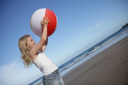 A young girl plays with a beach ball on the sand.