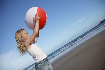 gevangen: Een jong meisje speelt met een strand bal op het zand.